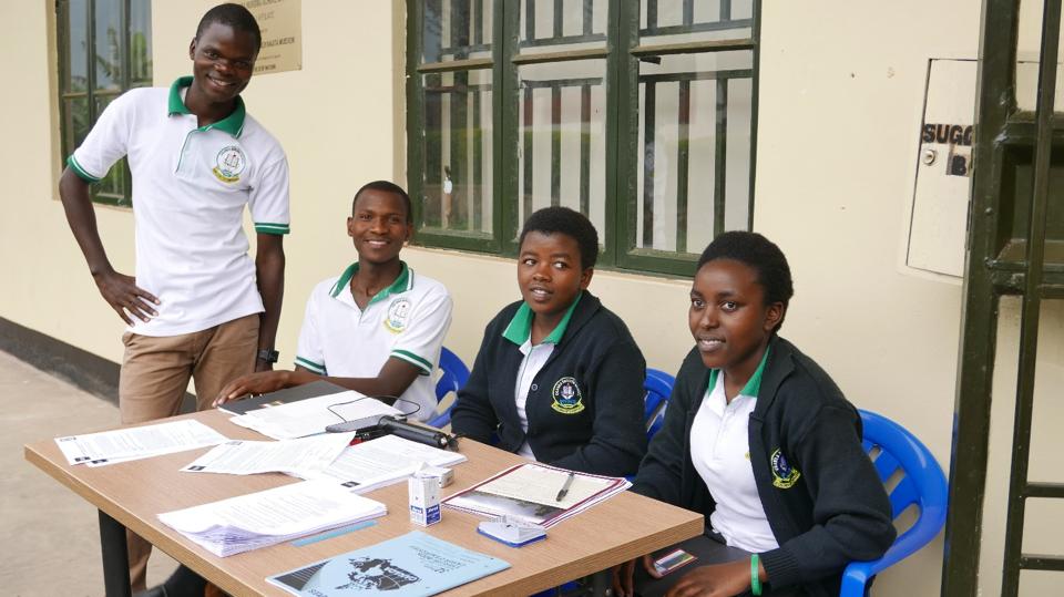 Student translators from the Uganda Nursing School Bwindi managing the workshop registration table.
