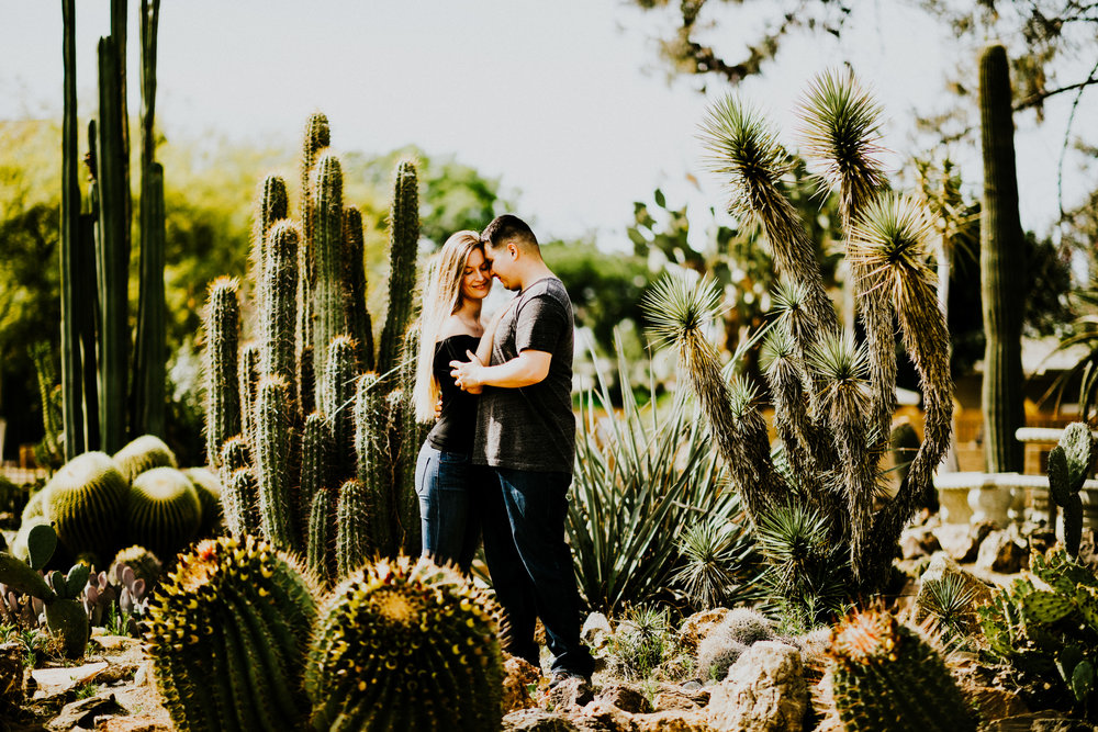 Guy and girl holding each other surrounded by cacti