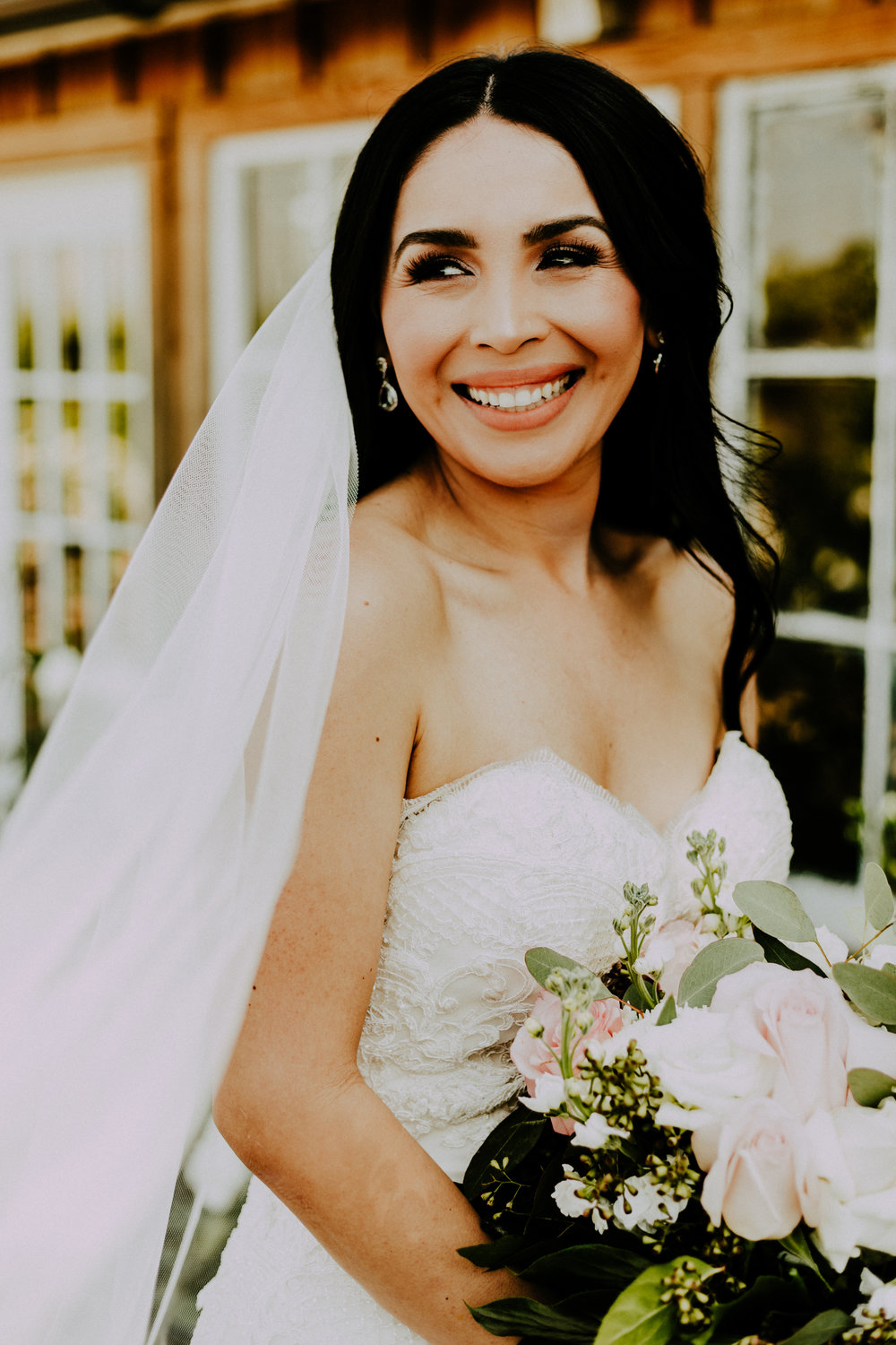 Bride smiling with veil and bouquet of beautiful flowers