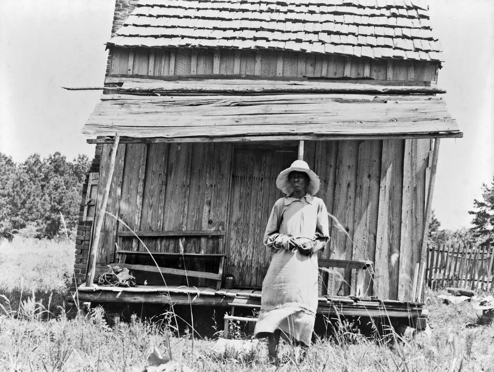 Sharecropper's wife and their home during the Great Depression. Dorothea Lange photograph.