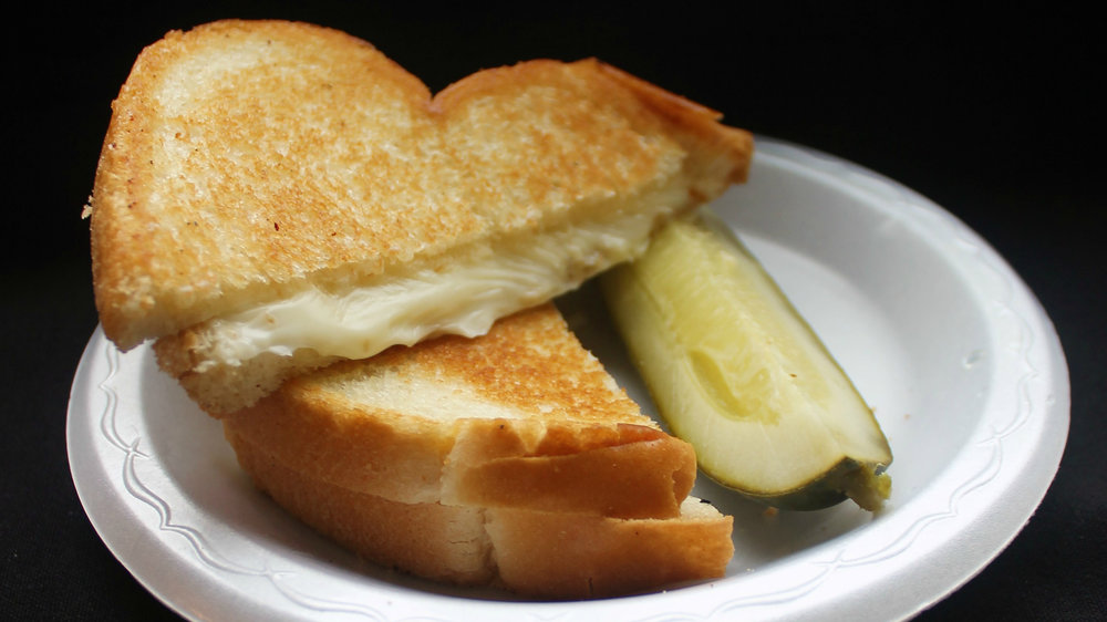 Classic Grilled Cheese - American cheese sandwiched between two slices of Italian bread and served with a pickle.