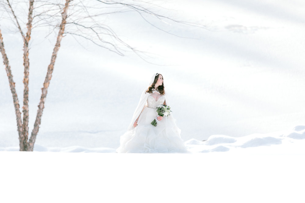 Bride in hooded cape for elegance in the snow as photographed by Kris Lenox
