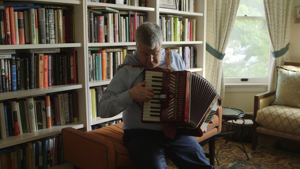 Daniel Handler playing the accordian in his study.jpg