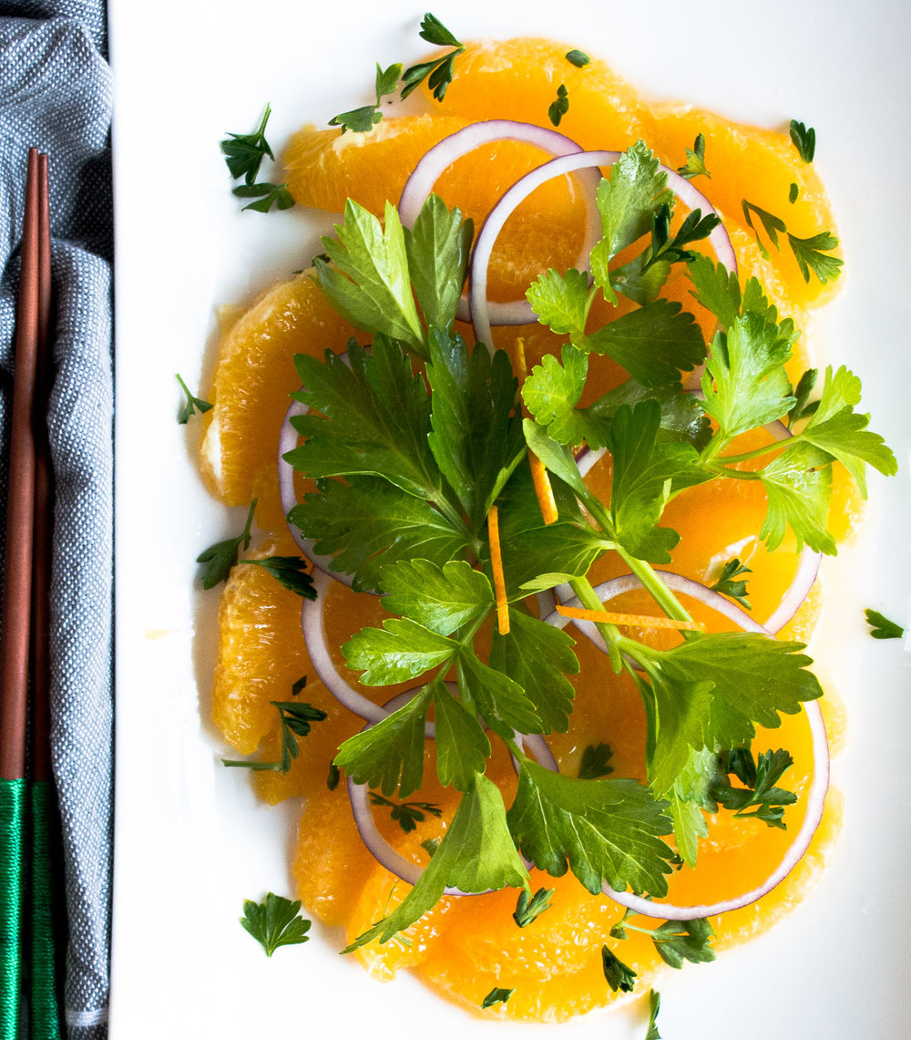 Layered orange salad. Oranges segments, red onion, young celery stalks and minced parsley.