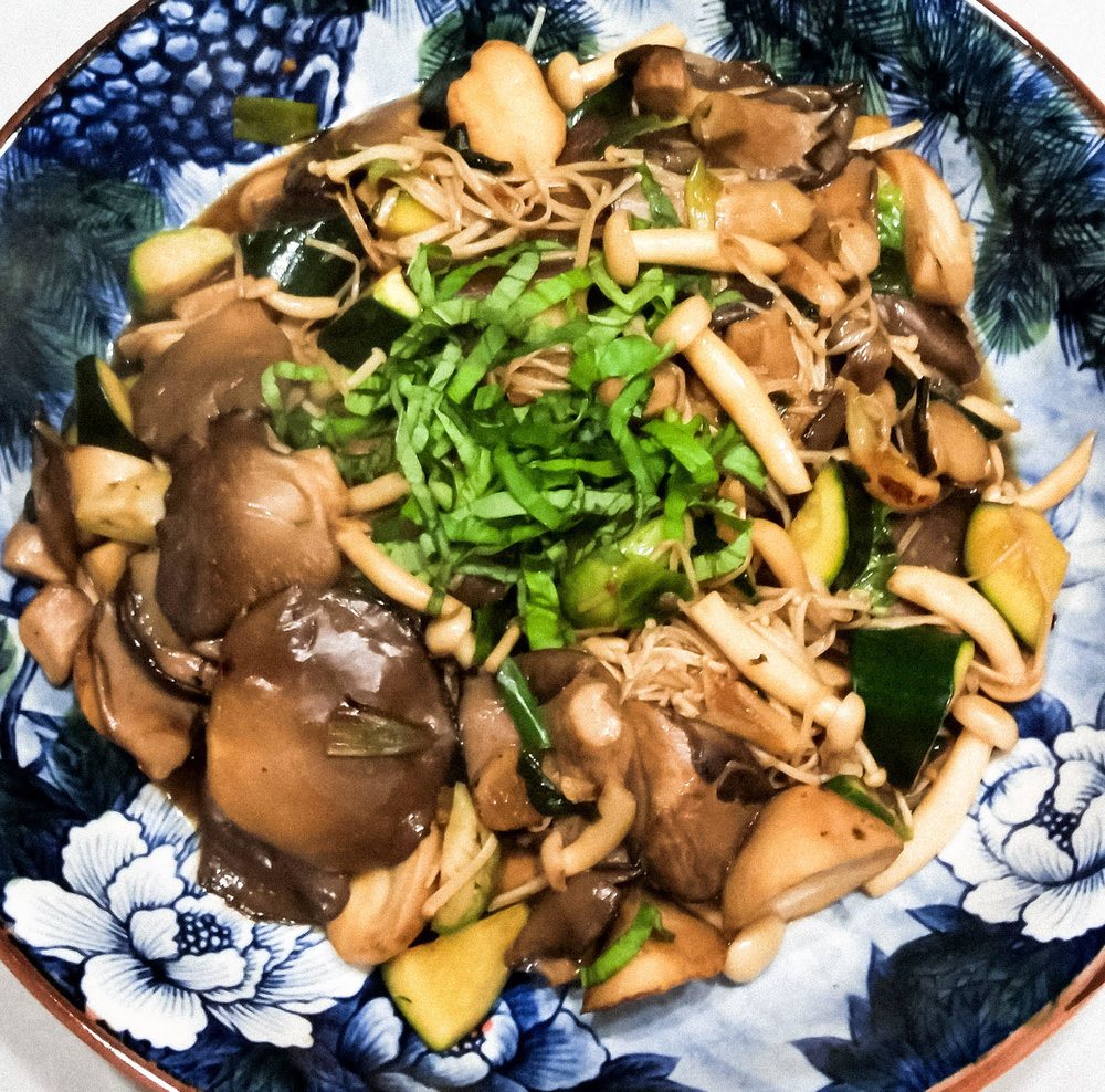 In serving bowl, Three-Cup Mushrooms with zucchini, topped with basil.