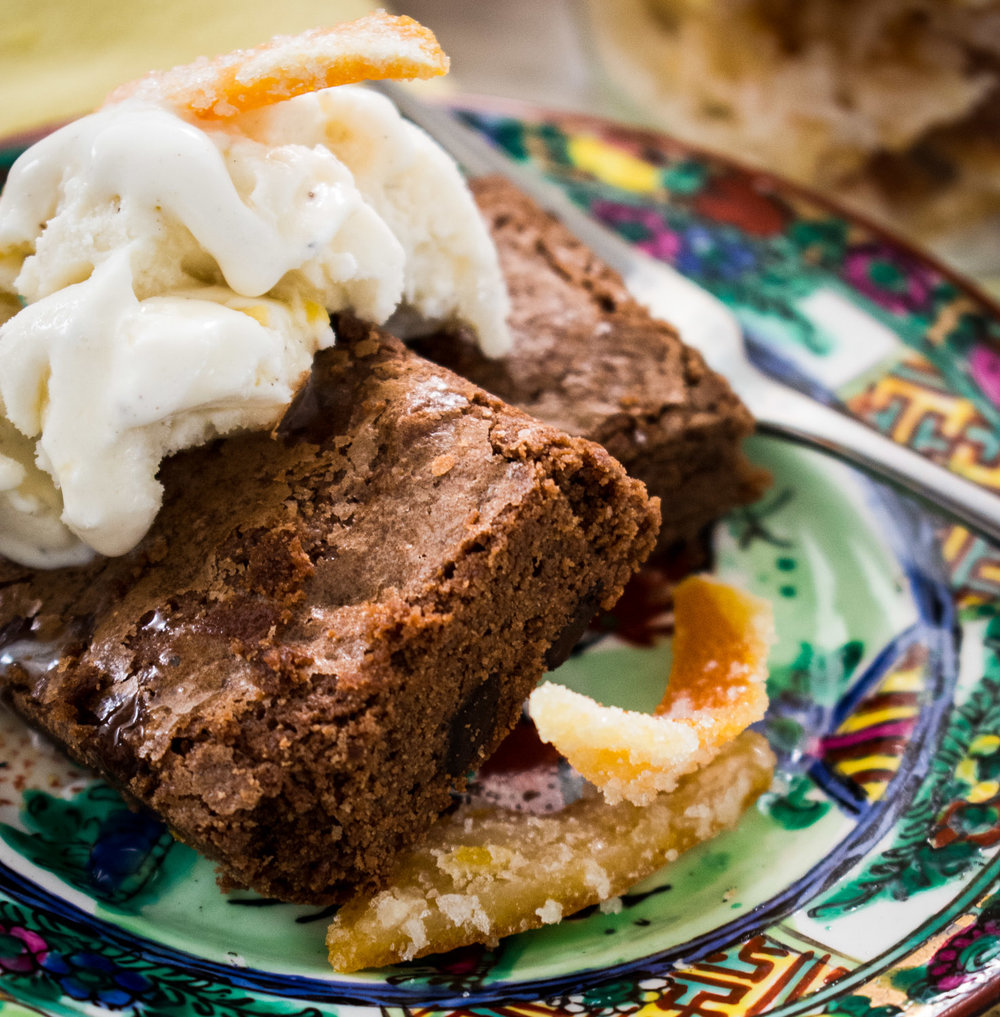 Orange brownies with ice cream, orange syrup and candied orange peel.