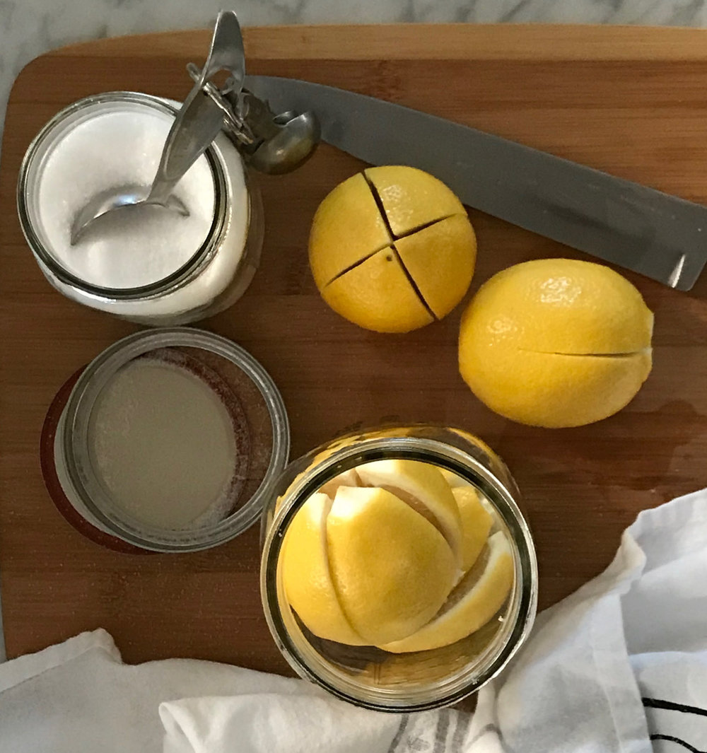 Putting salted lemons in a jar.