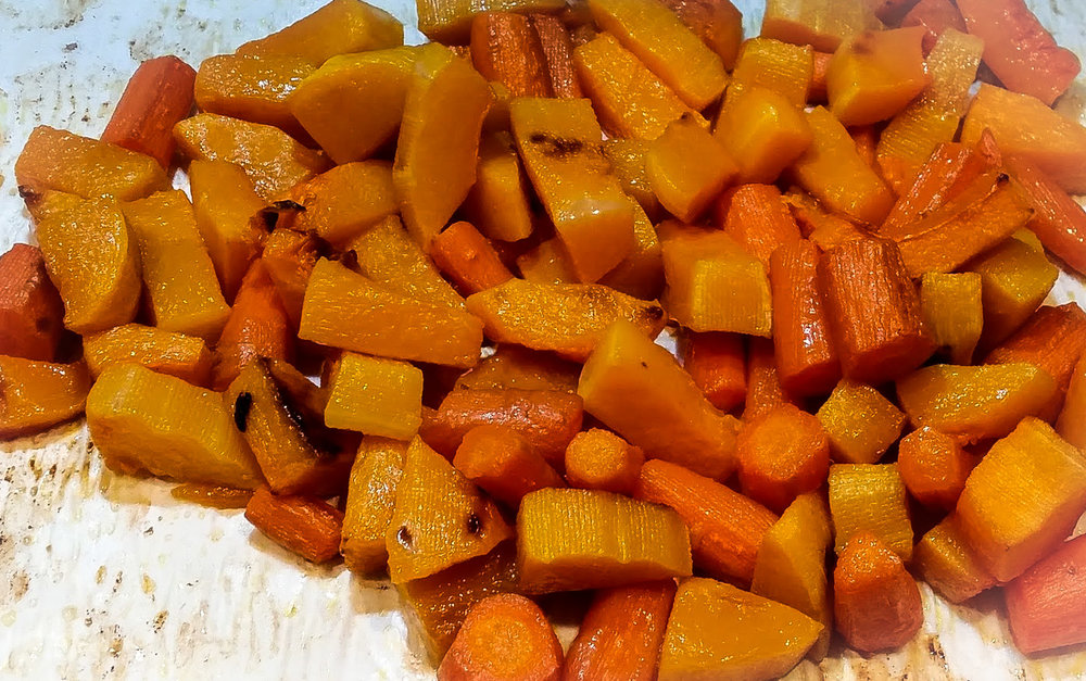 Sheet pan with caramelized butternut squash and carrots pieces.