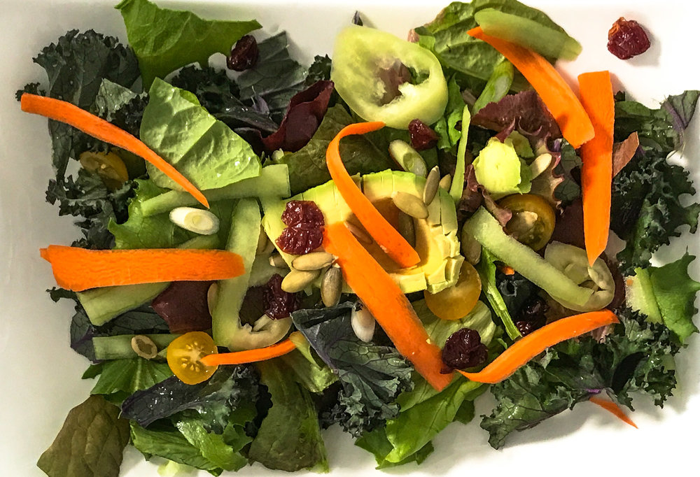 Composed salad of carrots, cucumbers, bell peppers and pepita seeds with tomatoes and cranberries on a bed of mixed greens with chopped kale