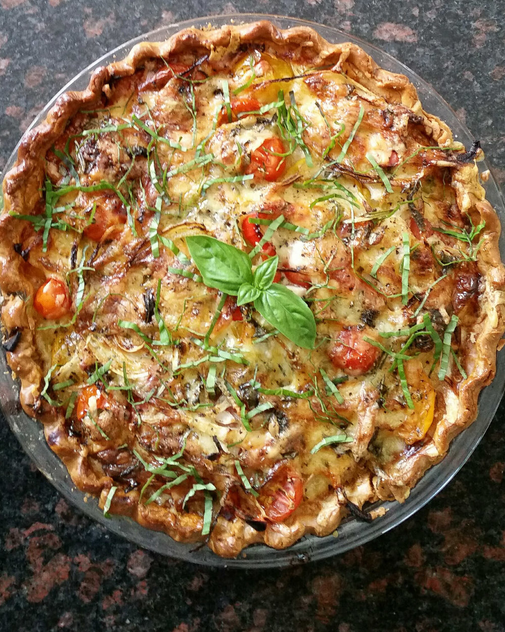 Yummy tomato pie topped with fresh basil.