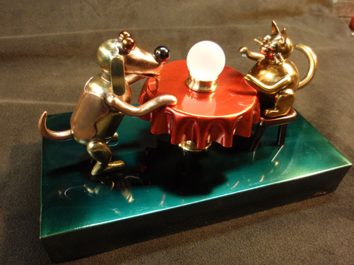 "A dog and a cat are in a seance to determine ""Who Will Be My New Owner"". It is made of brass and copper. The ""crystal ball"" in the center is lit by LED lights, and is constantly changing through thousands of colors by use of a microcontroller (computer chip). Also this was auctioned for the North Bay Humane Society."