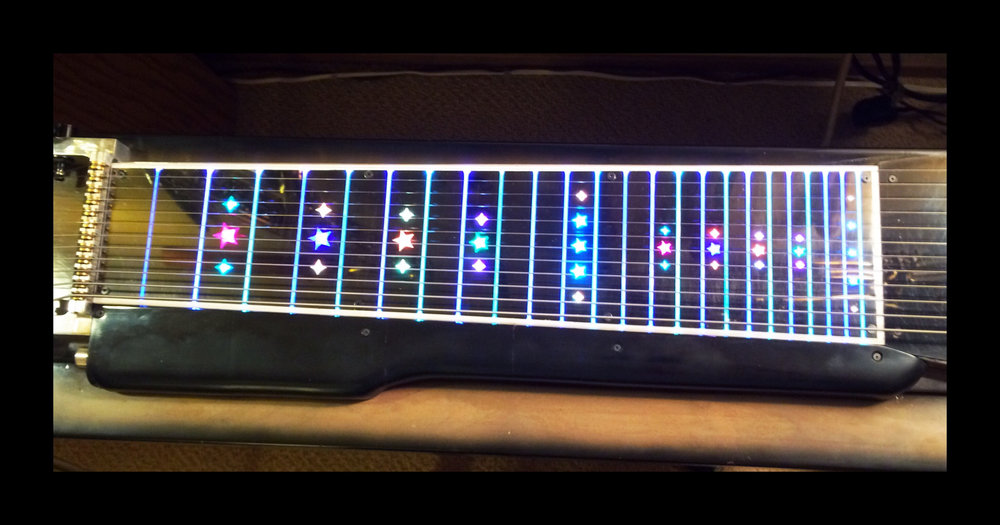 This is a lighted fretboard for the neck of my pedal steel guitar. I made it using a 3D printer for the black of the neck, the white edging, the clear covering over the stars, and the black cover over the electronics at the bottom. RGB (three color) LEDs light up the stars, and the frets via side-emitting fiber-optics.