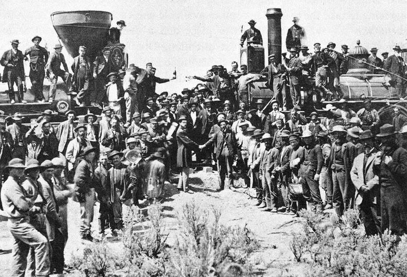 Workers celebrating the completion of the first transcontinental railroad during the historical Golden Spike Ceremony (1869)