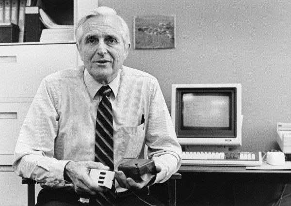 Douglas Engelbart holding the first mouse prototype first revealed in 1968