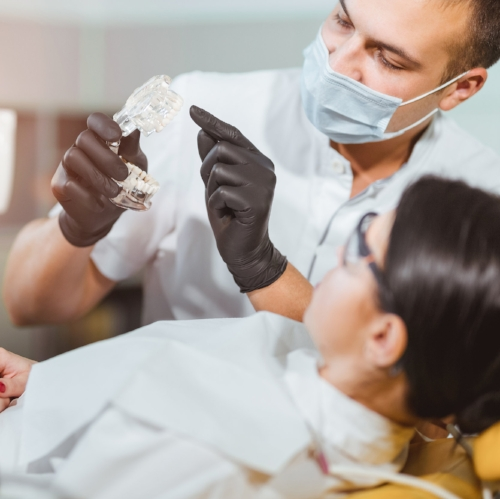 Dentist explaining oral appliance for sleep apnea to patient
