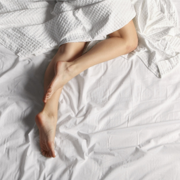 woman in bed with legs moving, restless leg