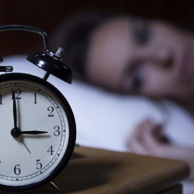 WoMAN with insomnia staring at alarm clock