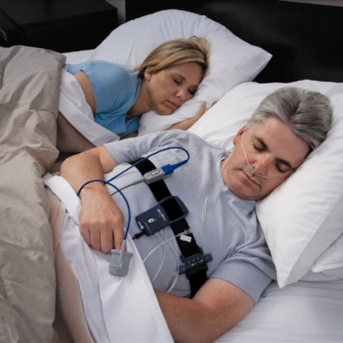 Man sleeping at home with home sleep study equipment