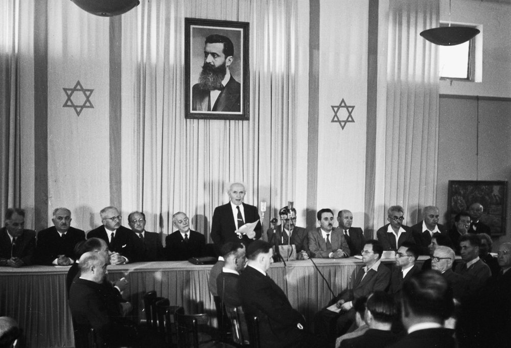 David Ben-Gurion, who engineered the founding of Israel and was its first Prime Minister, declaring independence beneath a portrait of Theodor Hertzl, the father of Zionism.