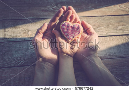 stock-photo-female-and-children-s-hands-hold-cookies-in-the-form-of-heart-on-a-wooden-table-top-sunlight-a-576677242.jpg