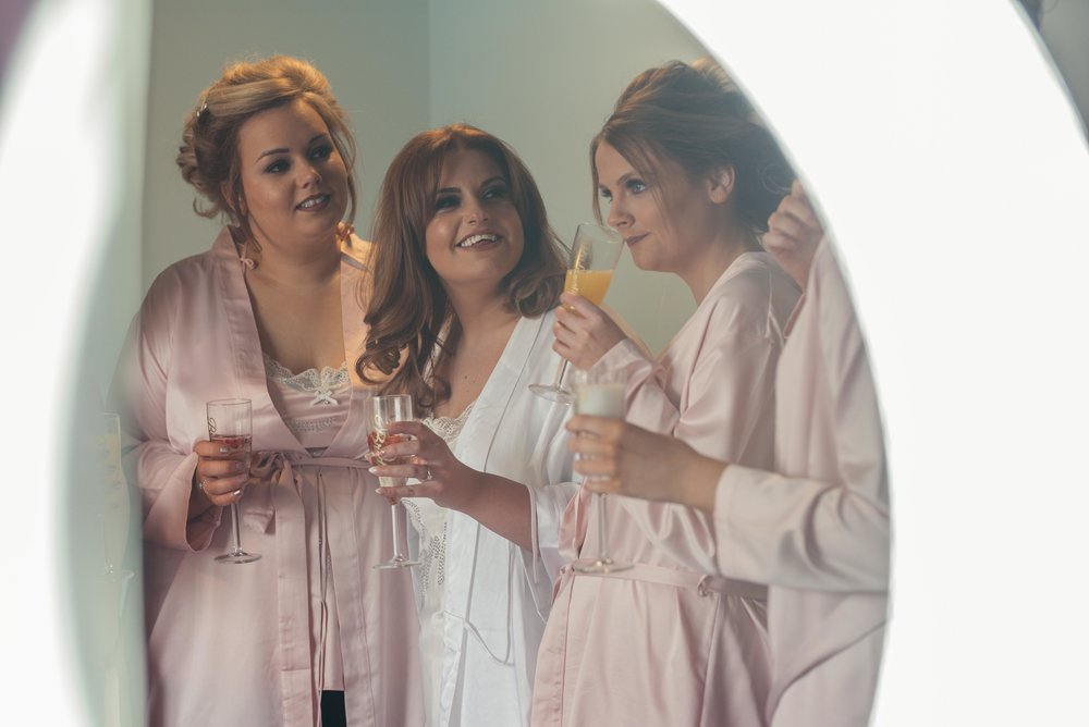 The bride and bridesmaids have a drink together during their wedding photography
