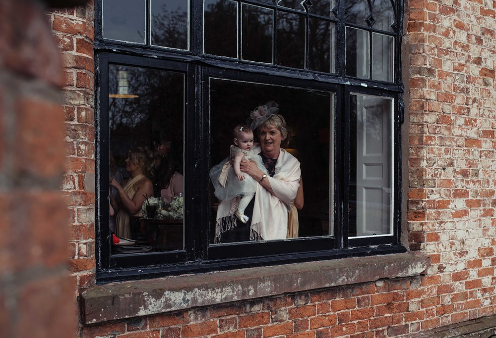 a wedding guest holds their young granddaughter against the window of the bar at crabwall manor so she can look outside