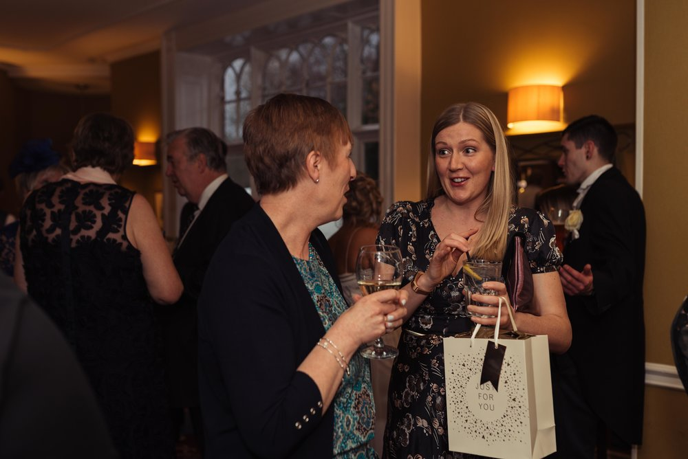 a wedding guest has a surprised look on her face talking to another of the guests