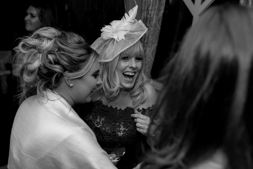the brides mother has a big laugh with two of her friends on the dance floor