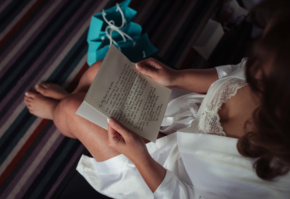 the bride sits on a sofa and reads a letter from her husband to be