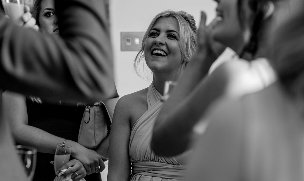 a bridesmaid shares a smile with other wedding guests during the drinks reception