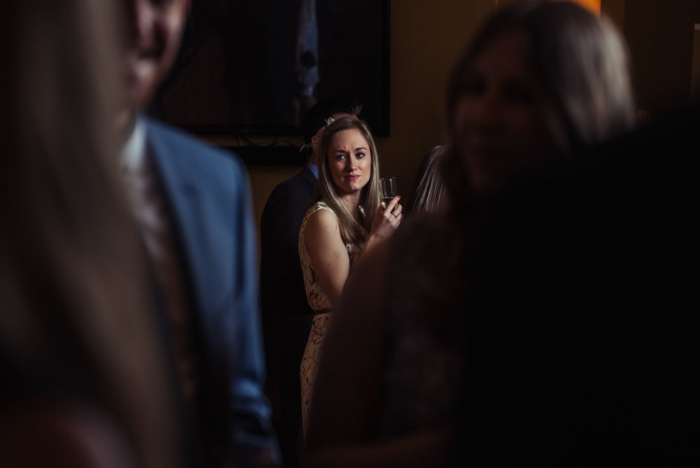 a wedding guest lit up with natural light in the bar