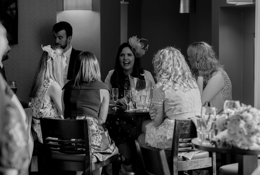 a group of wedding guests sit round a round table in the bar at Crabwall Manor