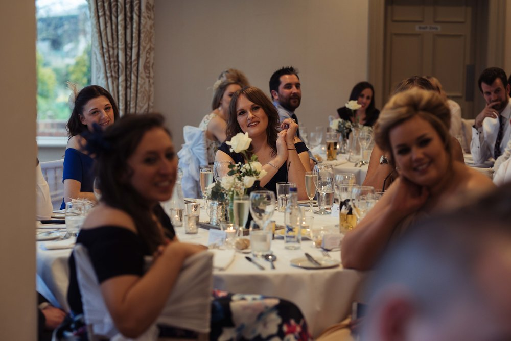 a wedding guest sits at the table during the wedding breakfast and smiles at the speeches