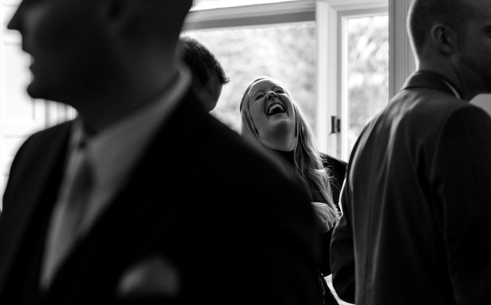 a wedding guest throws her head back in the air laughing at a joke in the bar of the wedding venue