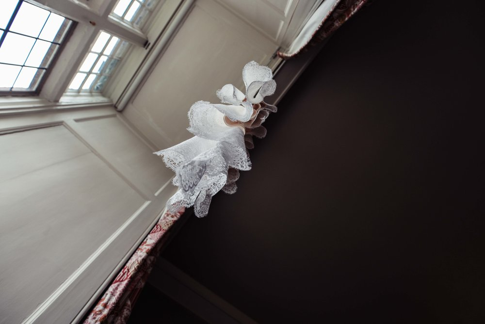 The brides dress hangs down from the window