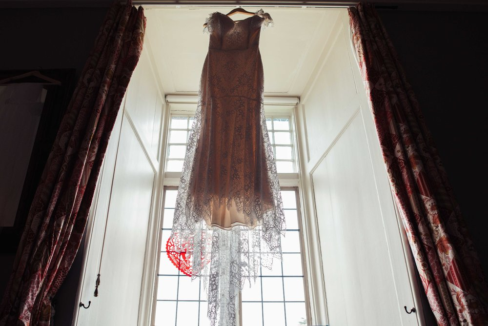 The brides dress hangs in a window at Askham Hall
