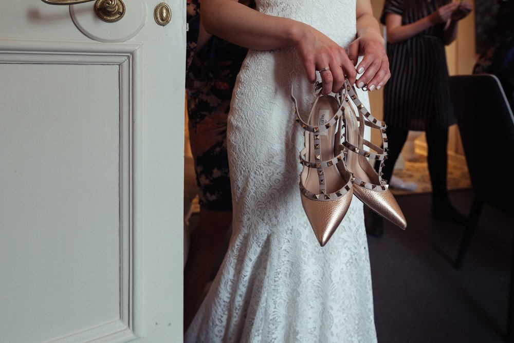 The bride holds her shoes as she stands behind the bathroom door in her room at Askham Hall