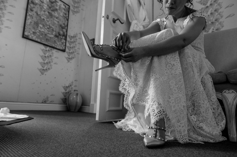 the bride fastens her shoes before leaving the room and heading over for the wedding ceremony