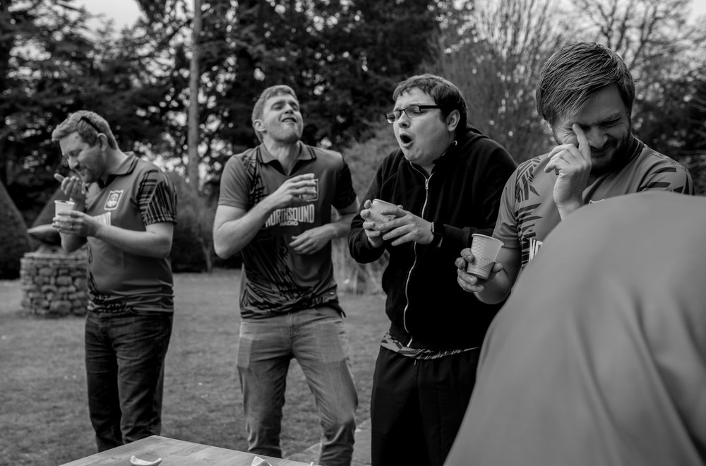 the groomsmen pull crazy faces as they are forced to drink something really horrible