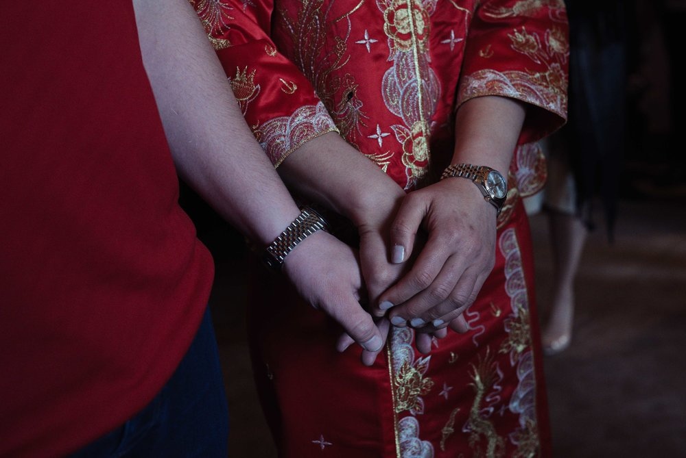 the bride and groom hold hands during the chinese tea ceremony