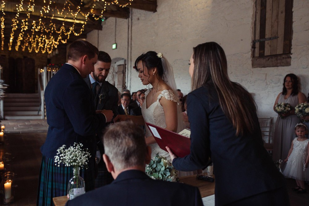 the bride and groom take the rings off the best man during their wedding ceremony