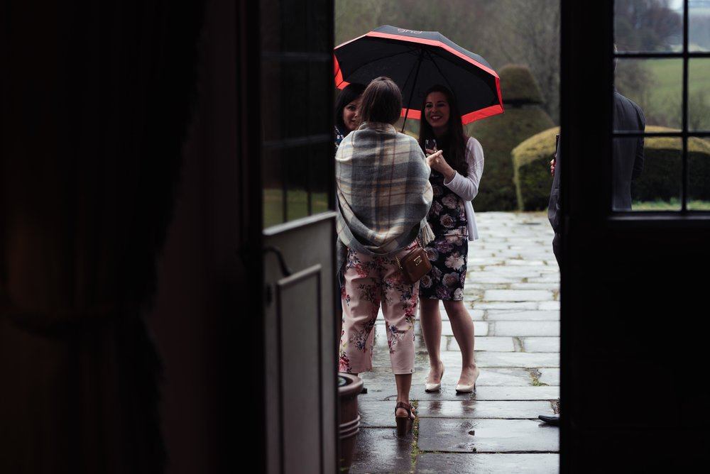Wedding guests brave the rain and stand outside with an umbrella