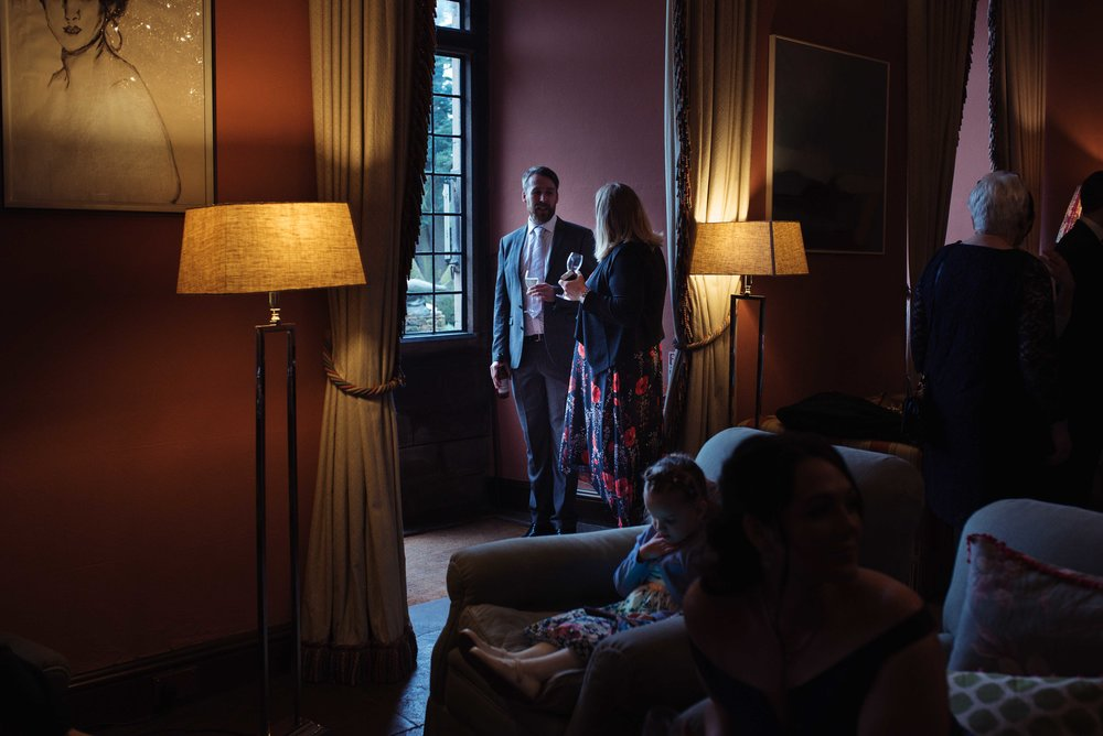 Two wedding guests stand in the doorway, they are lit with daylight coming in through the window