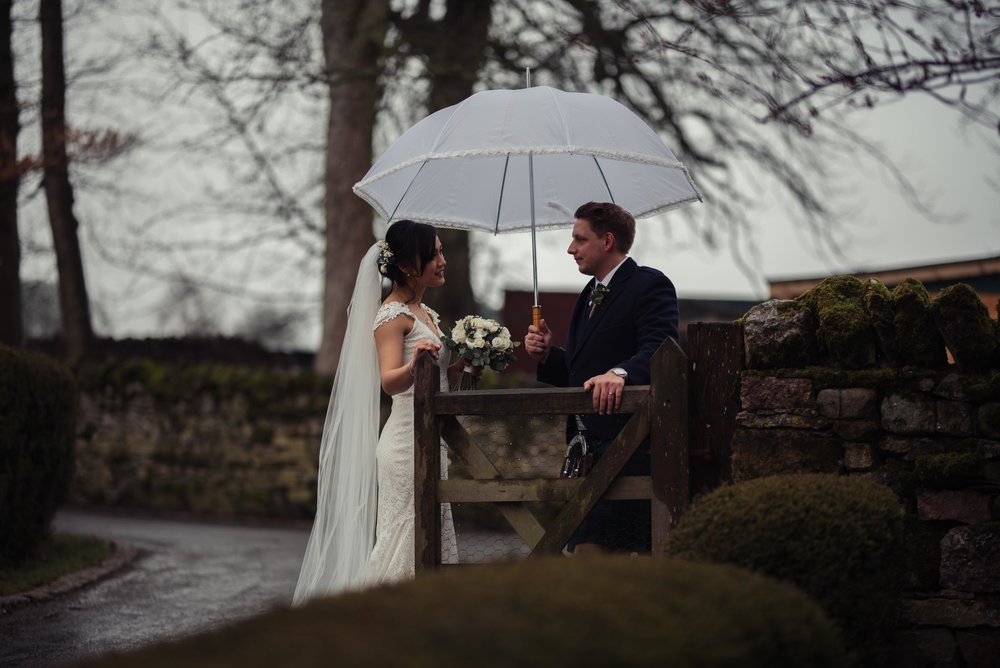 The bride and groom stand under a white umbrella for their wedding photography at Askham Hall