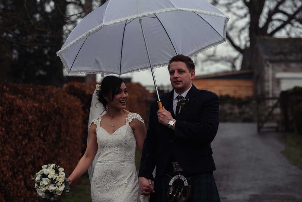 The bride and groom walking down from the barn to Askham Hall for their Lake District Wedding Photography