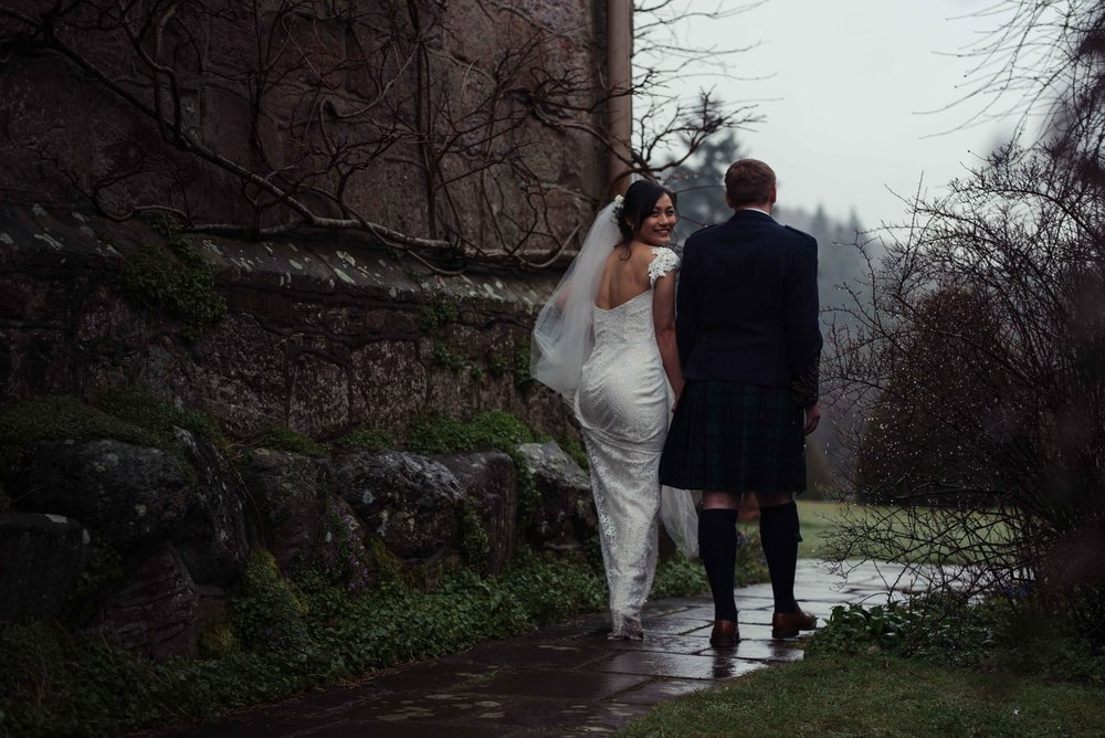the bride looks over her shoulder on her way round to the front of Askham Hall