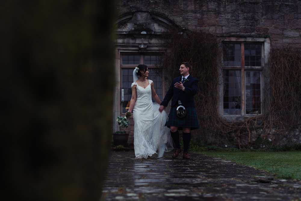 The bride and groom have a chat with each other as they walk away from Askham Hall