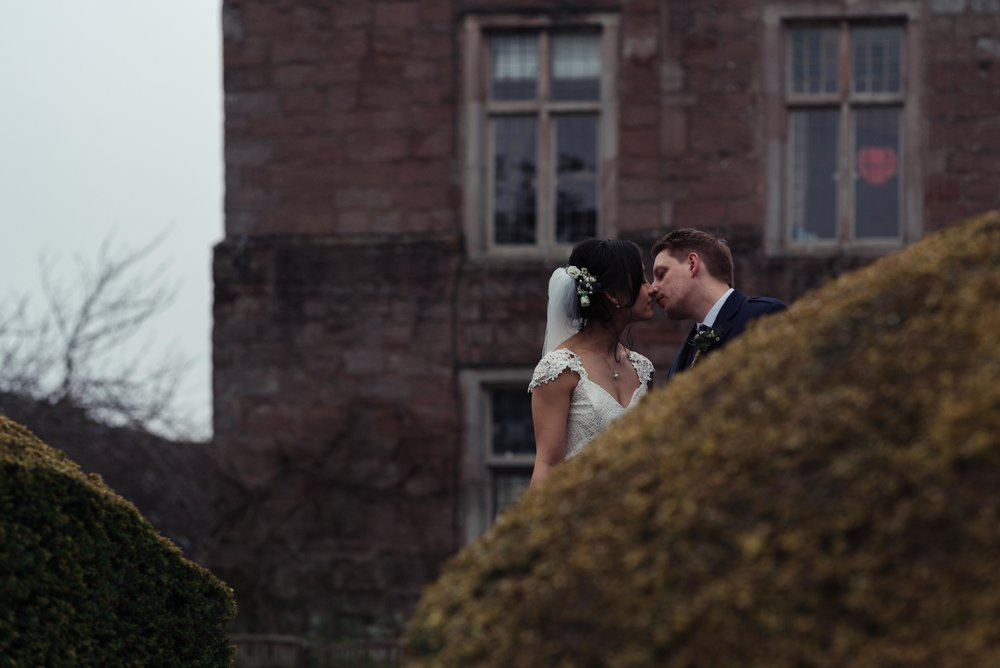 The bride and grooms head are visible above a bush at Askham Hall