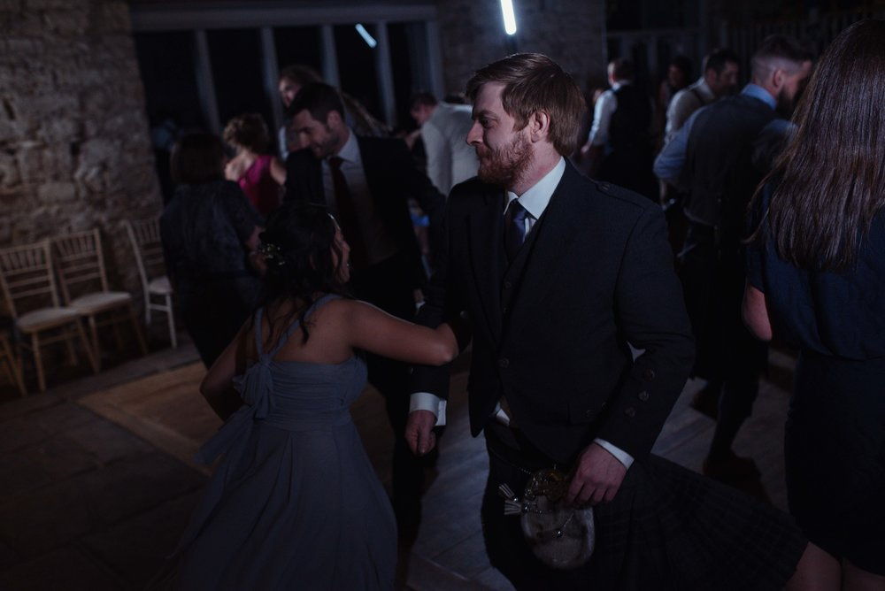One of the groomsmen is enjoying the scottish dancing on the dance floor
