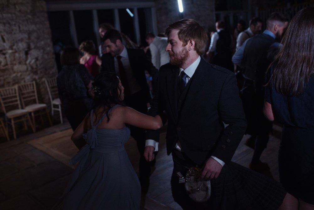 One of the groomsmen is enjoying the scottish dancing on the dance floor